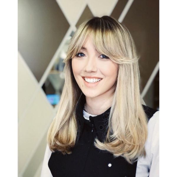 Subtle Wavy Long Layered Hairstyle with Dark Roots and Side Swept Bangs