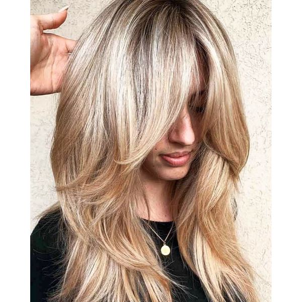 Voluminous Blonde Long Layered Hairstyle with Full Bangs