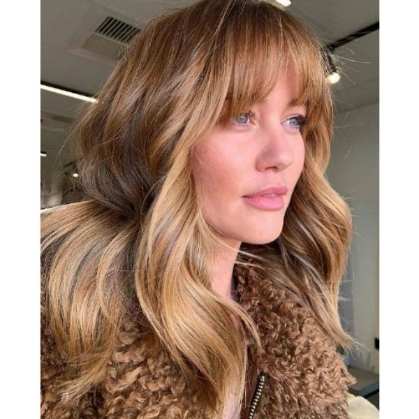 Copper Blonde Hairstyle with Straight Bangs and Waves