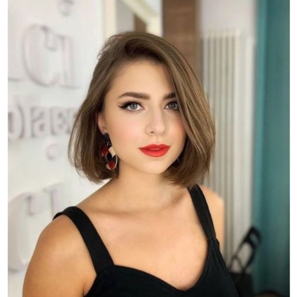 Chin Length Bob Haircut For Oval Face With Side Swept Strands
