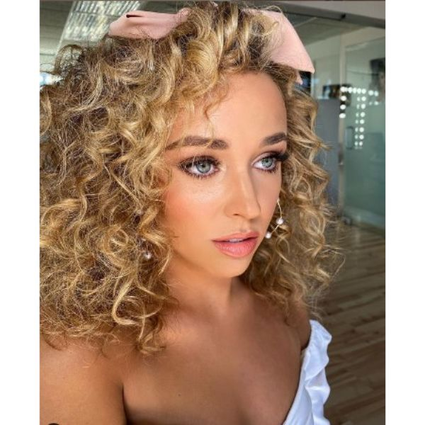 Curly Hairstyle For Blonde Hair With Pink Ribbon