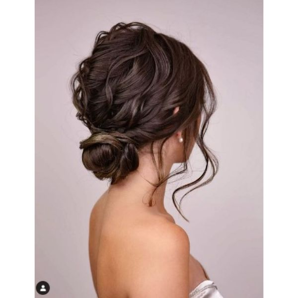 Dark Wavy Textured Wedding Updo With Falling Strands And Side Bun