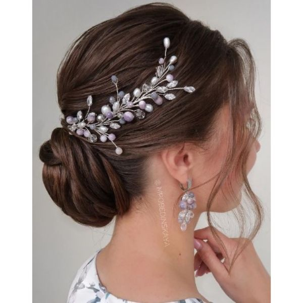 Elegant Low Twisted Bun With Floral Pieces And Falling Strands