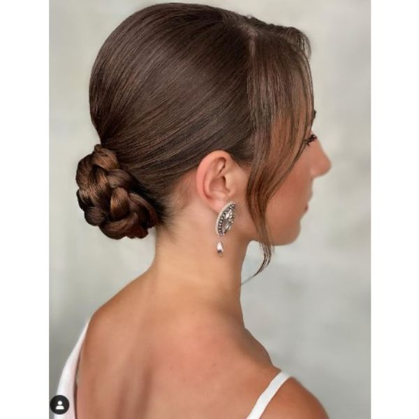 Smooth Low Braided Bun With Falling Strands