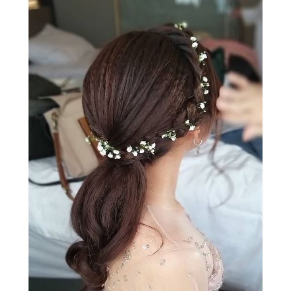Swirling Low Ponytail With Crown Braid And Wedding Flowers Hairstyle