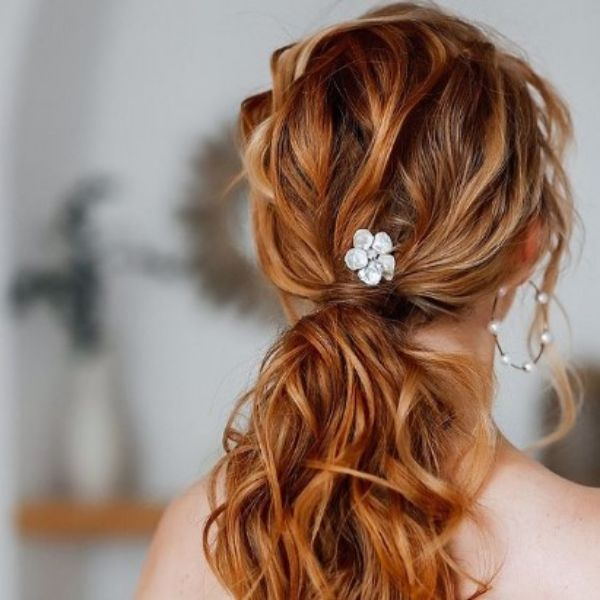 Textured Low Ponytail With Flower Pin For Medium Hair