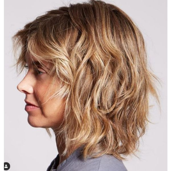 Warm Blonde Medium Haircut For Wavy Hair With Side-swept Strands