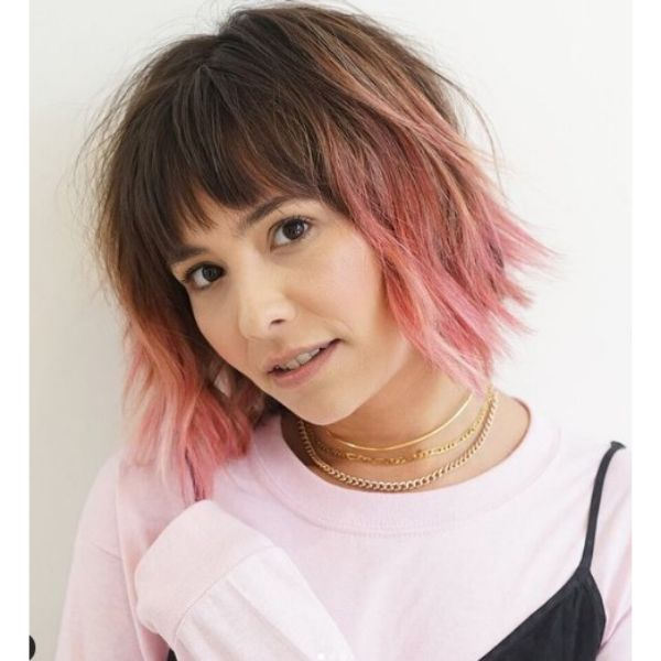 Wavy Medium Haircut With Peach Pink Highlights And Straight Bangs
