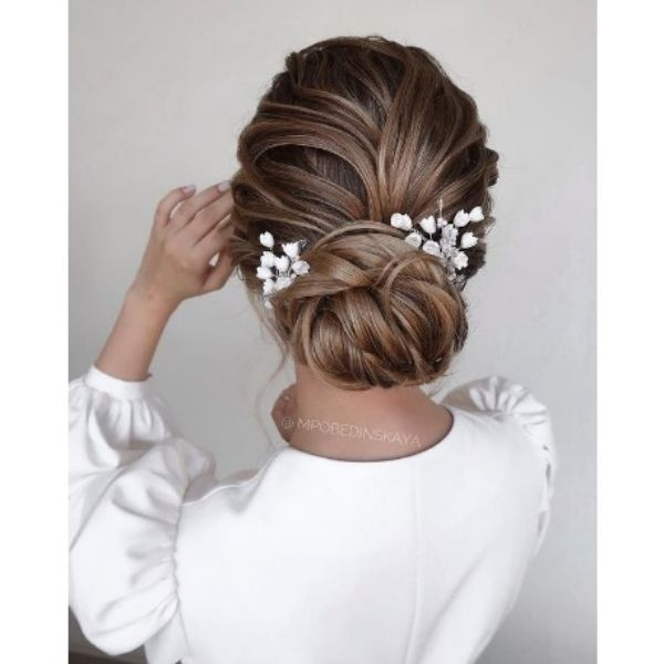 Wedding Updo With Twisted Strands And White Floral Pieces