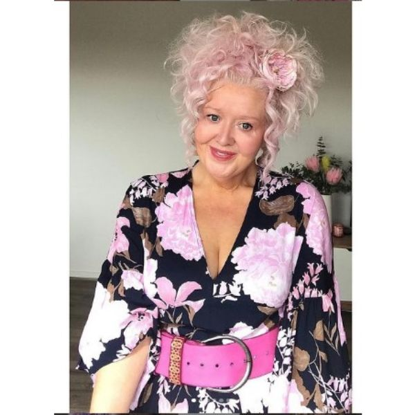Messy Pink Curly Updo With Floral Accessory And Falling Strands