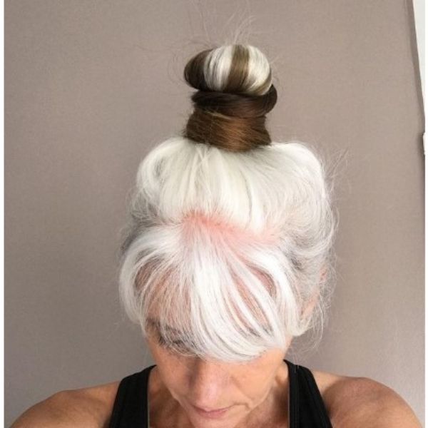 White Sleek High Bun With Brown Insertions Hairstyle For Older Women
